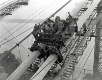 The main cables have been spun and are being compacted and banded. The bridge's four cables are made from individual strands of wire laid one on top of the other -- enough wire to stretch halfway to the moon.