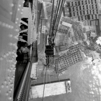Looking down from the top of a tower leg, ironworkers are erecting the struts and braces that tie the legs of the tower together.