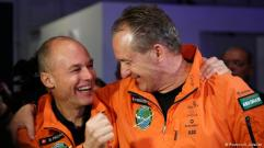 Piccard and Borschberg in orange jumpsuits