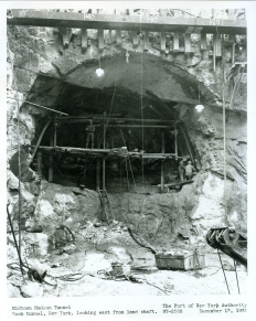 "Once land on the west side of Manhattan had been cleared of old tenement buildings, engineers excavated a construction shaft to provide vertical access to tunnel operations, including staircases on one side and electrical cables on the other for electricity and pipes carrying compressed air to keep the Hudson River from rushing into the tunnel. Within this shaft, workers known as ""Sandhogs"" assembled the cutting shield, weighing over 400 pounds, to initiate the burrowing beneath the Hudson. Holes were first drilled at the face of the tunnel, and then the drill holes were loaded with explosives and detonated."