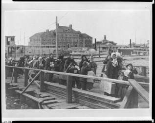 Emigrants coming up the boardwalk from the barge, which has taken them off the steamship company's docks. The building in the background is a newly-opened hospital. The ferry boat in the mid-ground of the photo runs from New York to Ellis Island.