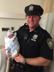 Life renewed itself in the World Trade Center PATH station as Port Authority Police Officer Brian McGraw holds baby girl Asenat Abdrabo whom he helped deliver when her mother went into labor at the PATH station. The event was immediately hailed as the first birth at the WTC site since 9/11
